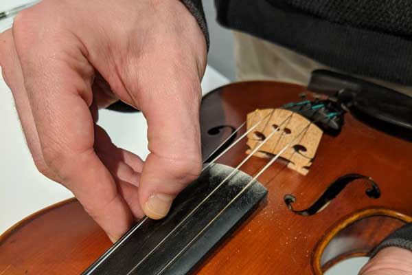 Pluck the violin strings to assess how closely they sound like the tuning tone